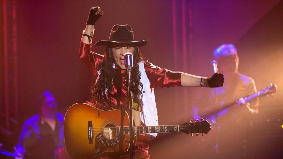 Une chanteuse est derrière un micro et tient une guitare.