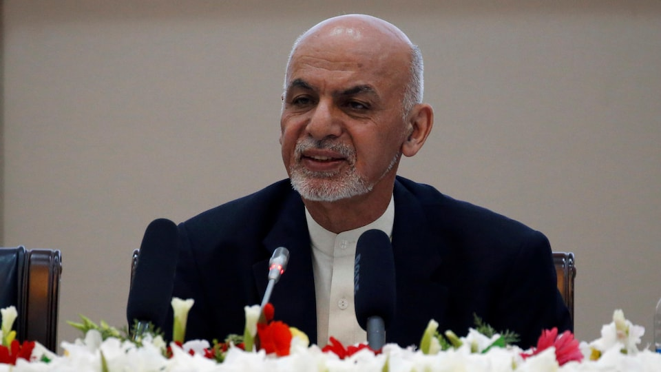 L'homme se tient assis, face à deux micros, lors d'une conférence à Kaboul.
