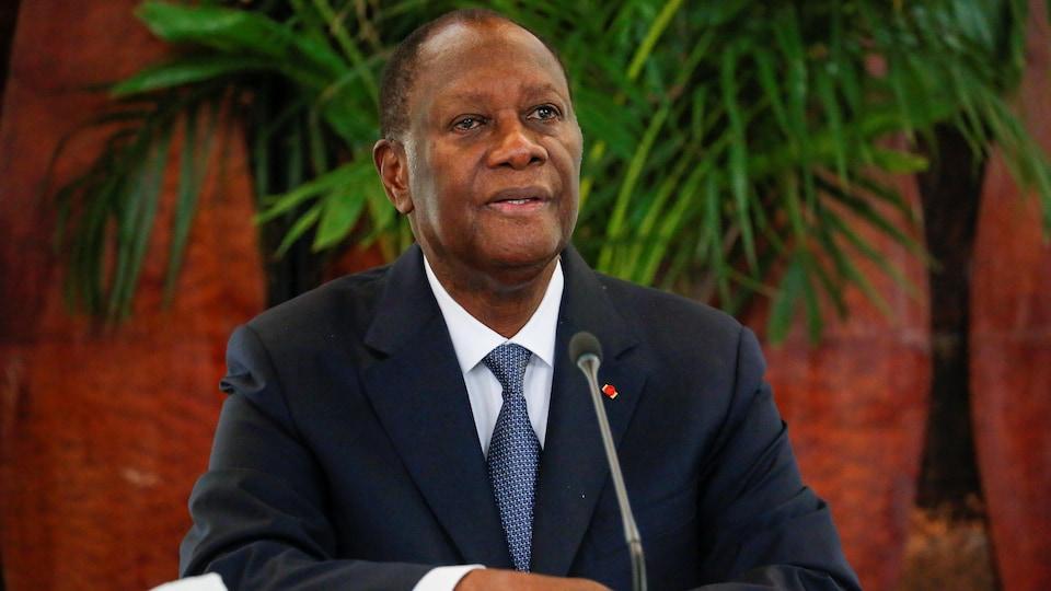 Alassane Ouattara est assis à une table de presse.