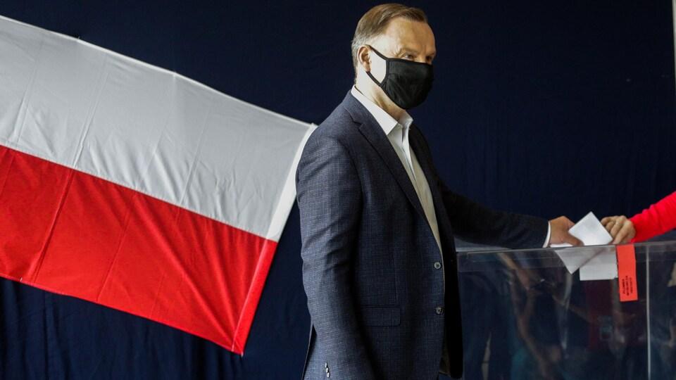 Le président sortant Andrzej Duda glisse son bulletin de vote dans l'urne à Cracovie.