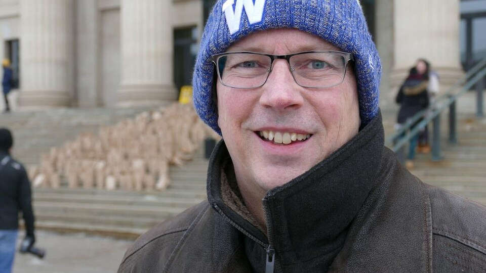 Plan épaules de James Bedford souriant devant le palais législatif du Manitoba.