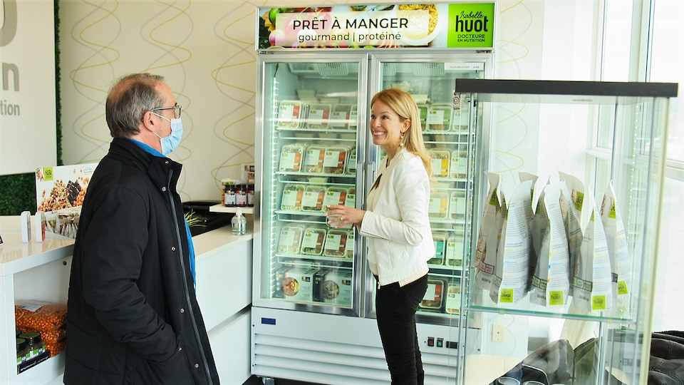 Denis Gagné et Isabelle Huot devant un réfrigérateur contenant des plats de prêt-à-manger.