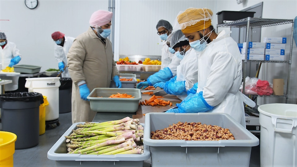 Des employés préparent des plats de prêt-à-manger dans une cuisine.
