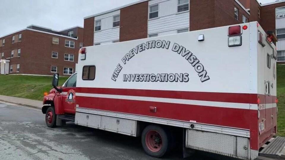 Camion rouge et blanc stationné devant un immeuble à logements.