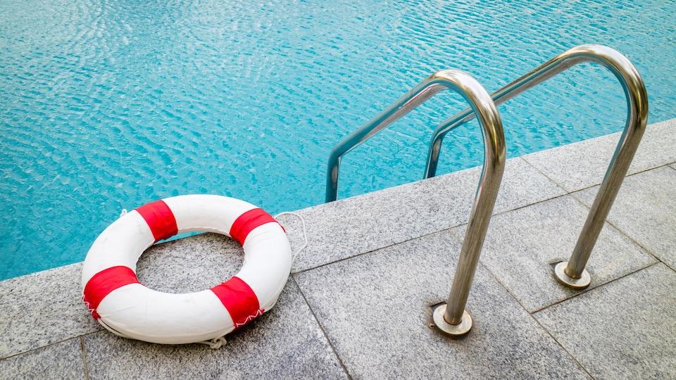 Une bouée de sauvetage rouge et blanche déposée en bordure d'une piscine creusée.