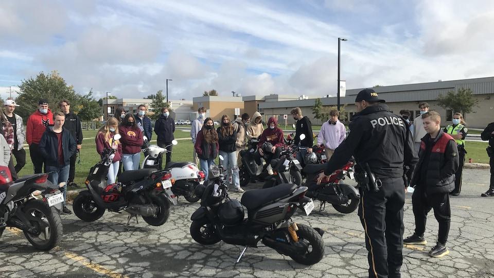 Un policier montre un élément sur un scooter à un élève.