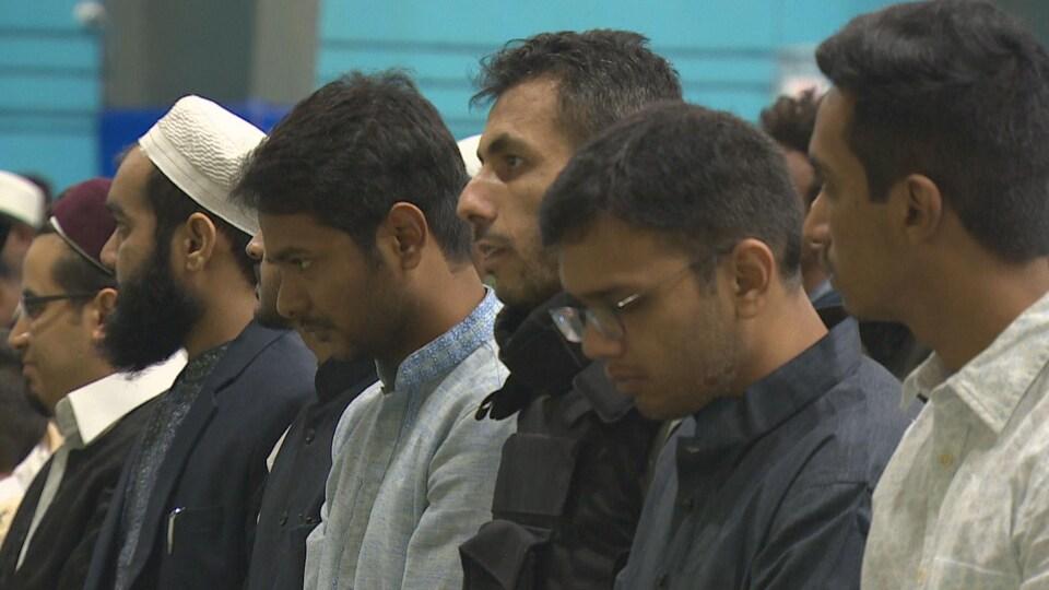 Plusieurs hommes se tiennent debout pour les prières. Un homme au centre porte un gilet pare-balles.