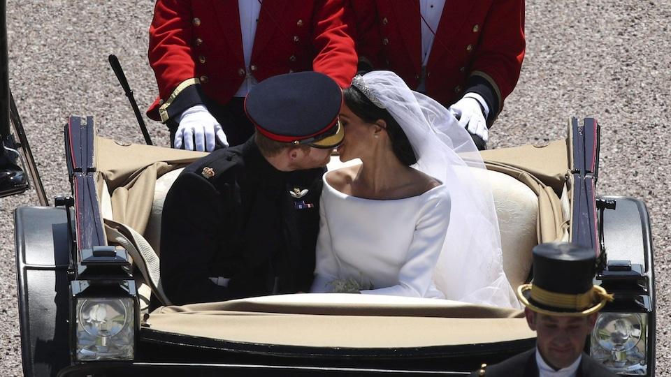 Le prince Harry en uniforme et Meghan Markle, en robe de mariée, échangent un baiser.