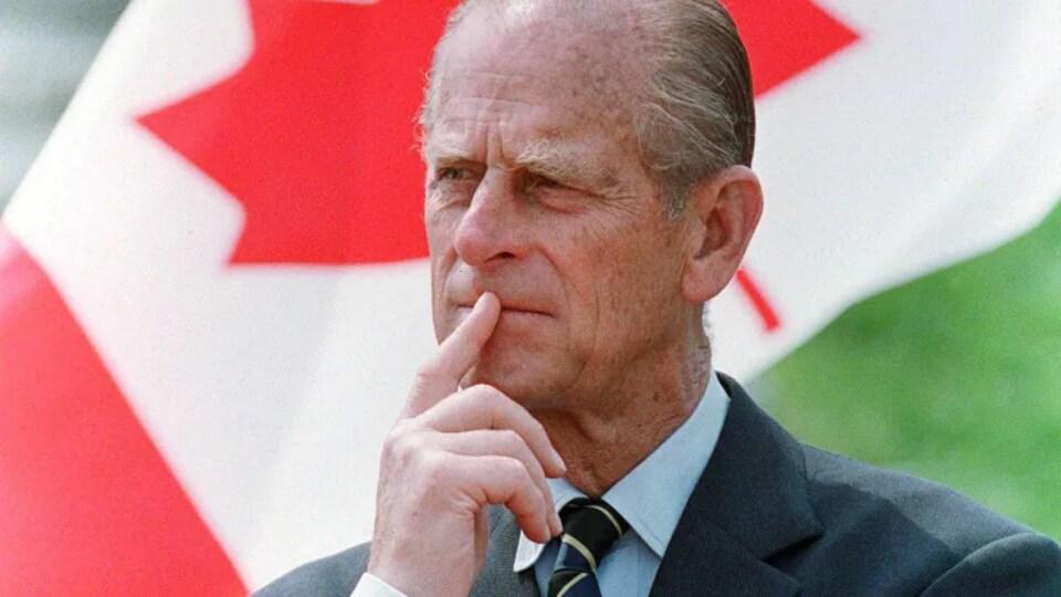 Le prince Philippe devant le drapeau canadien.
