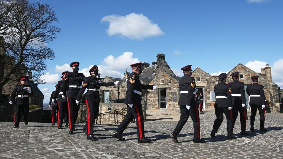Des membres de l'armée britannique marchent en rang.