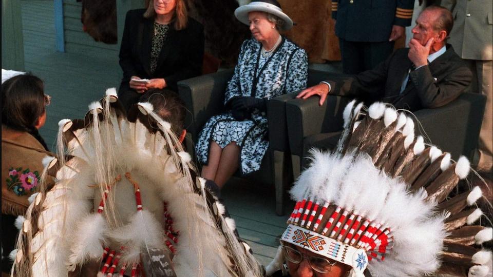 La reine et le prince discutent avec des chefs autochtones, dont deux portent une coiffe traditionnelle.