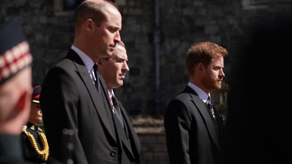 Des hommes en veston, l'air sérieux, fixe le sol ou droit devant eux.