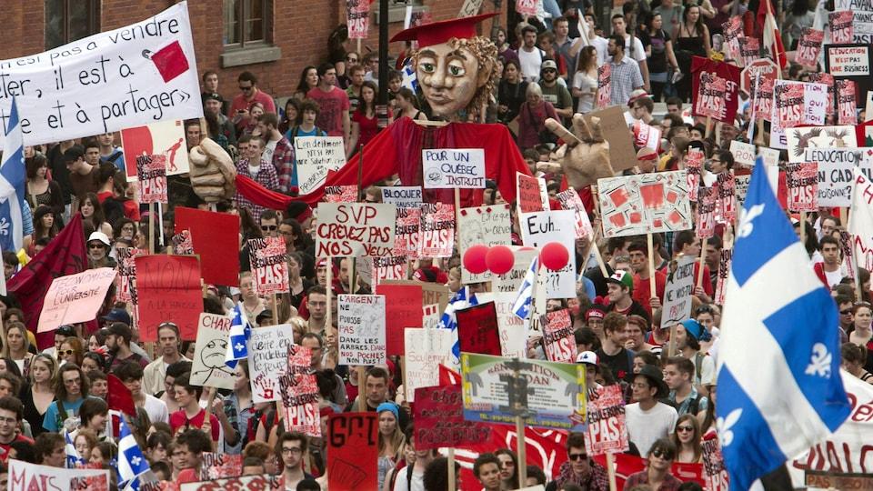 Une marée de manifestants et de pancartes envahit une rue du centre-ville de Montréal.