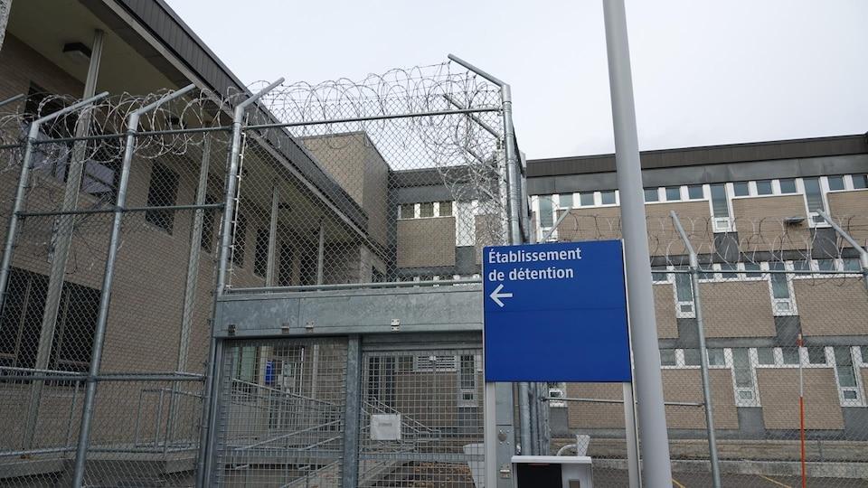 Un panneau indique l'entrée du centre de détention de New Carlisle, entouré de clôtures munies de fils barbelés.