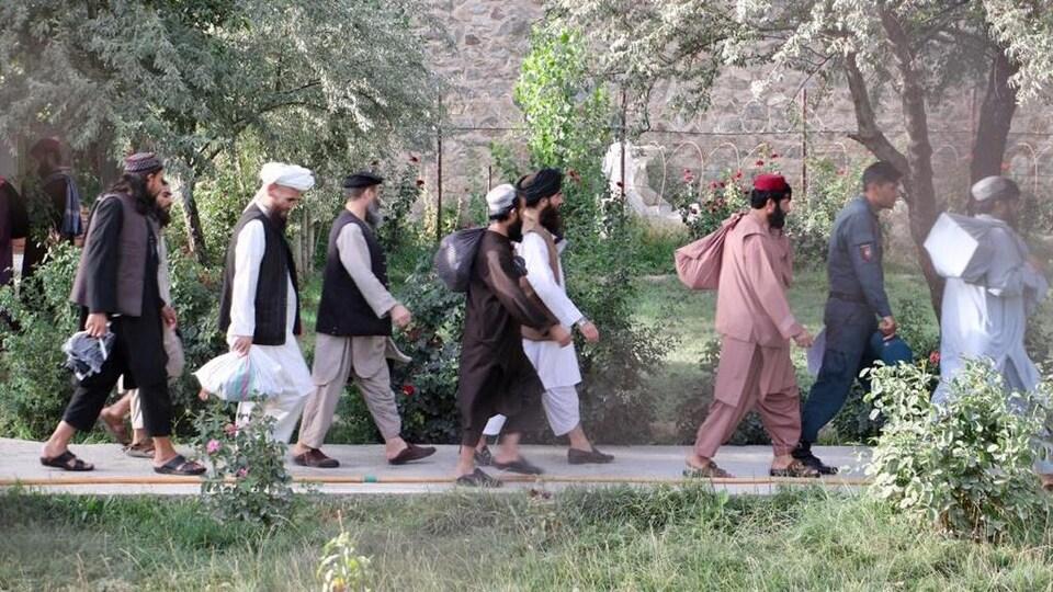 Des hommes marchent à la file.