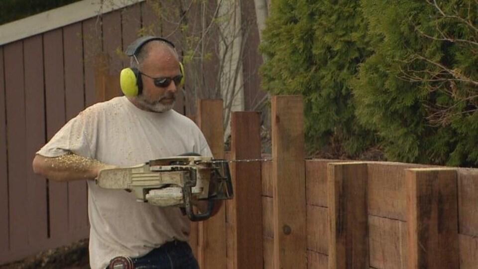 Scott MacTavish scie une clôture.