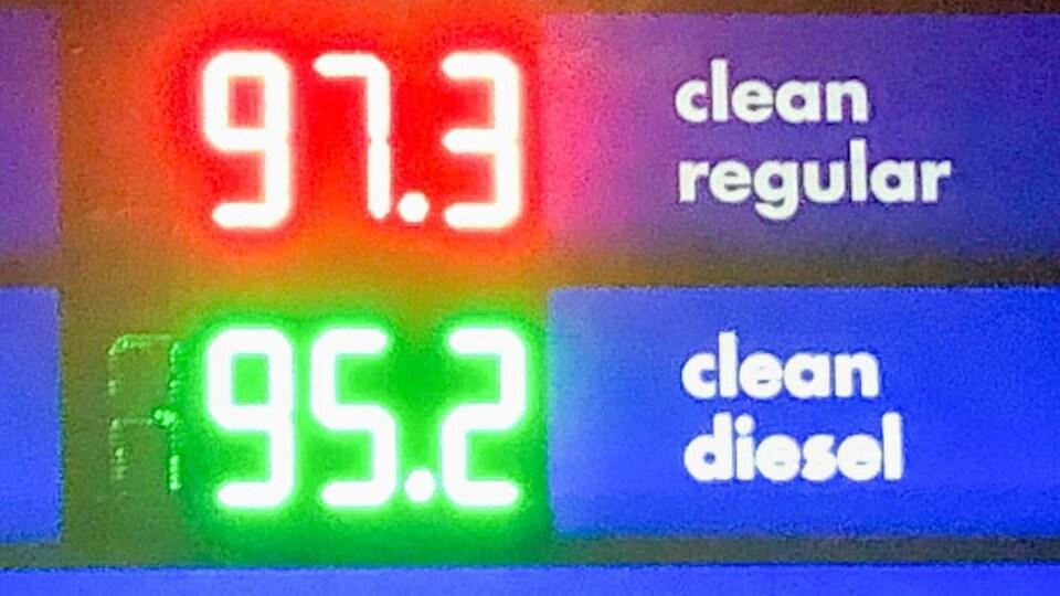 Une affiche indique le prix de l'essence à 97,3 sous le litre.