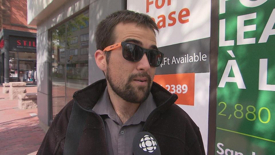 Une jeune homme portant la barbe et des lunettes soleil.