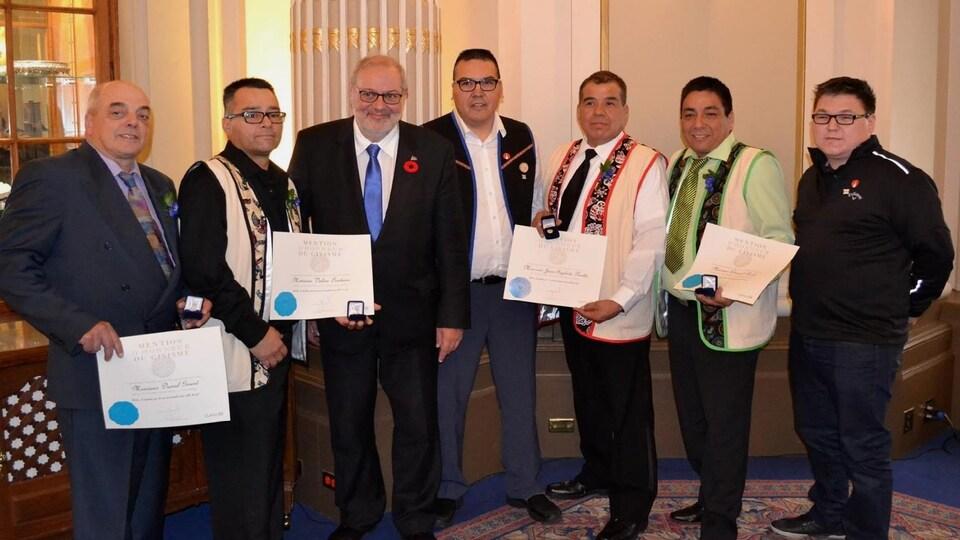 Les lauréats tiennent le certificat et la médaille reçue.