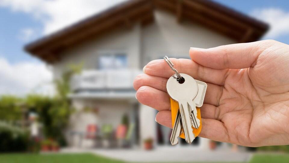 Une main qui tient des clés devant une maison.