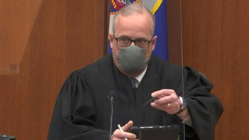 Le magistrat, togé et masqué.
