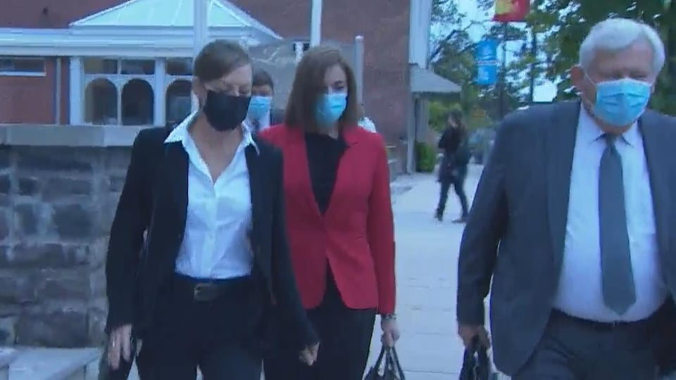 Une femme en tailleur rouge entre deux avocats.
