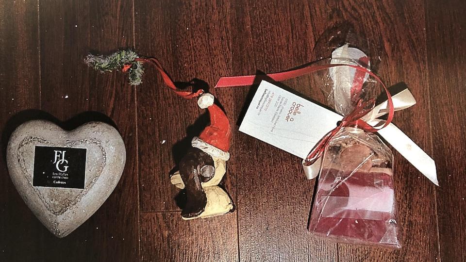 Trois objets, dont un coeur, une décoration de Noël et un sachet, sont déposés sur une table.