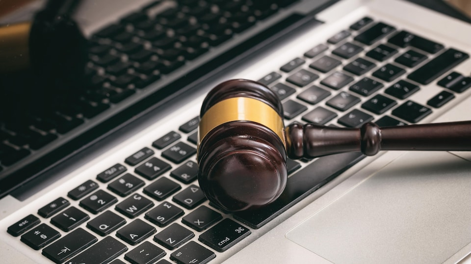 Un marteau de juge posé sur un clavier.