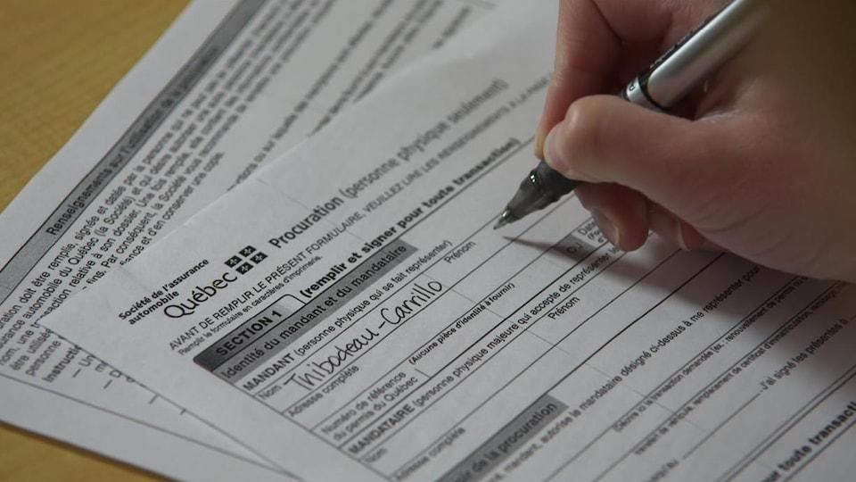Une personne remplie un formulaire de la SAAQ.
