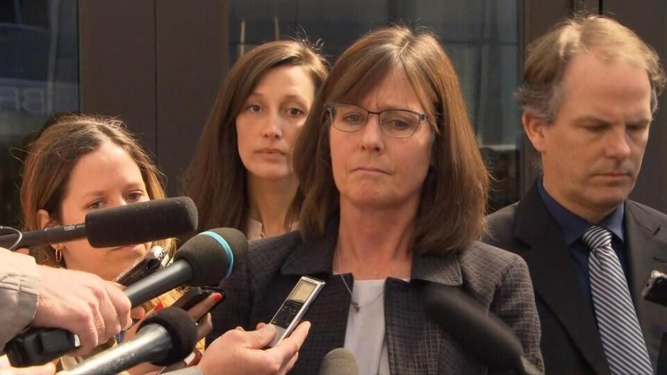 La procureure principale dans le dossier, Barbara Mercier, entourée de journalistes lors d'un point de presse à l'extérieur.