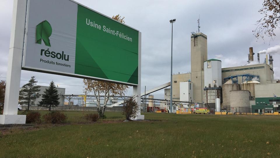 Une affiche de l'entreprise indique le nom de l'usine. En arrière plan, il y a l'usine.