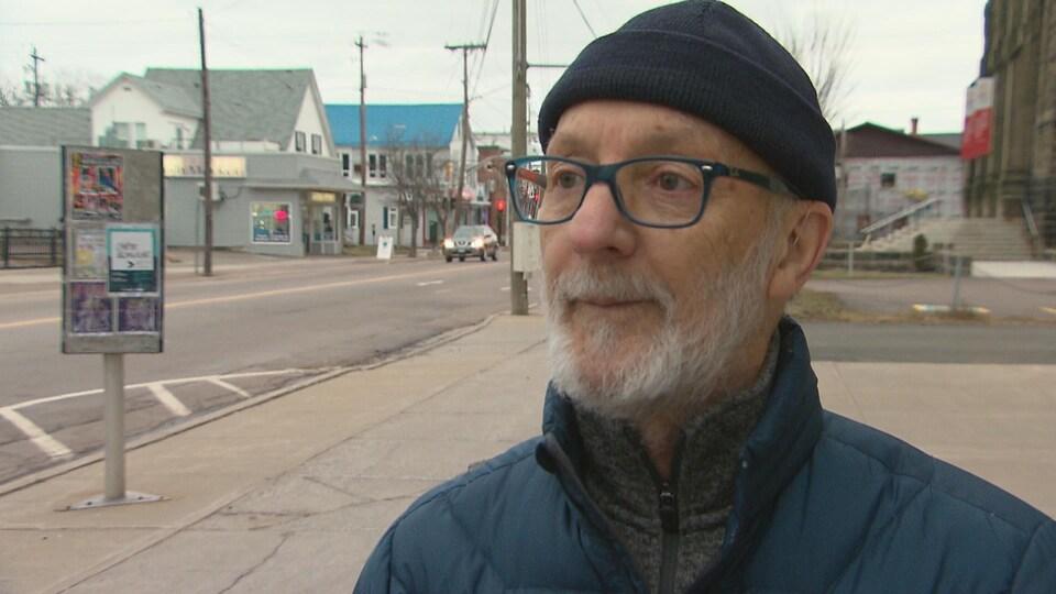 Jean-Claude Basque en entrevue sur un trottoir au centre-ville de Moncton