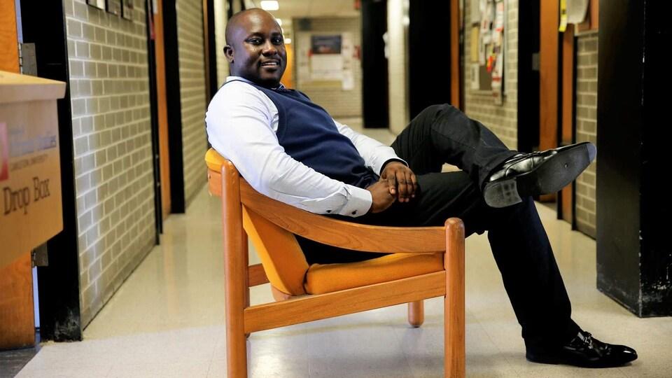 Pius Adesanmi est assis sur une chaise dans un corridor d'université.