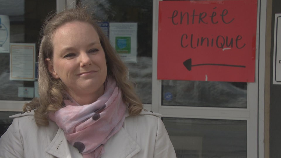 Une femme se trouve devant l'entrée d'une clinique médicale de Gatineau.