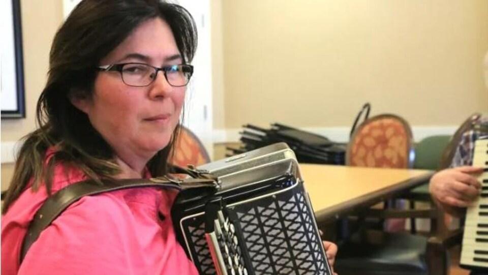 Une femme pose avec un accordéon.