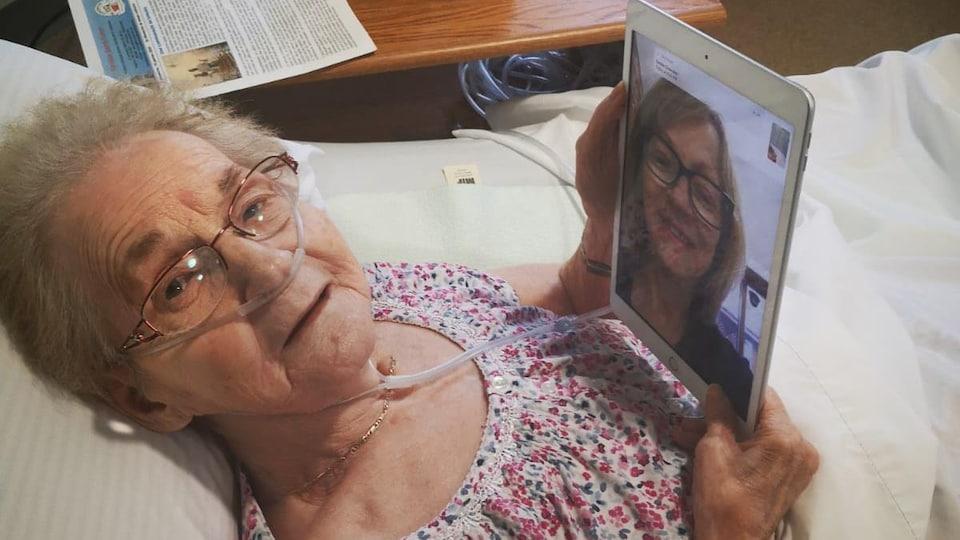 Une femme âgée dans son lit parle avec sa fille par l'entremise d'une tablette électronique.