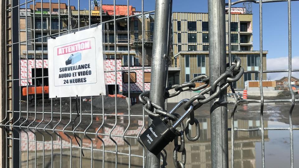 Un cadenas ferme des barrières devant un chantier de construction