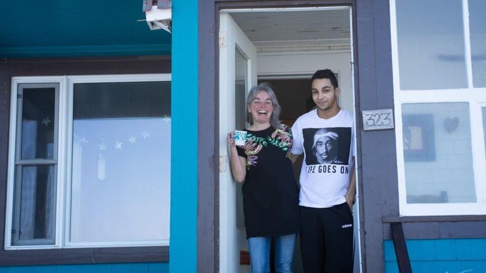 Une femme et un jeune homme à la porte. la femme a un grand sourire.