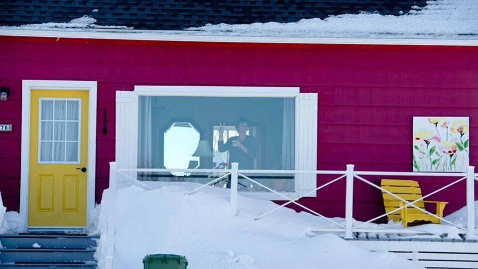 Une dame salue à sa fenêtre.