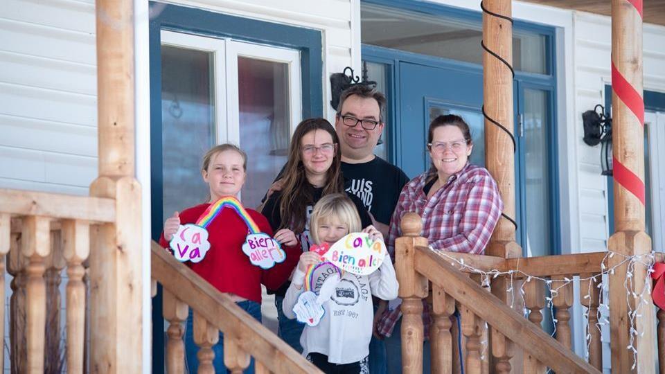 Une famille, de deux parents et trois enfants sourient sur leur galerie.