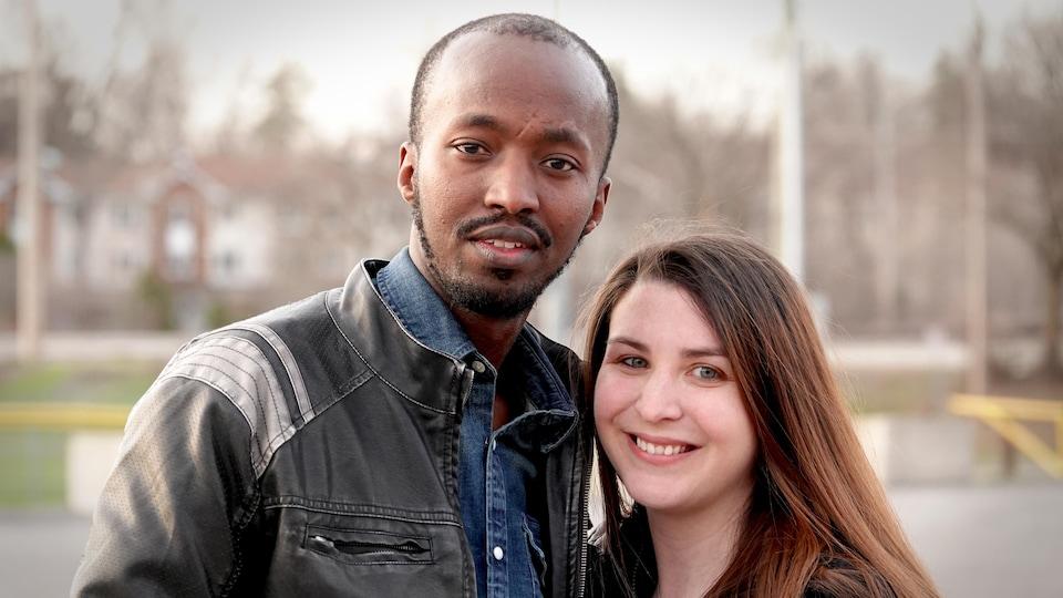 Un homme et une femme souriant à la caméra.