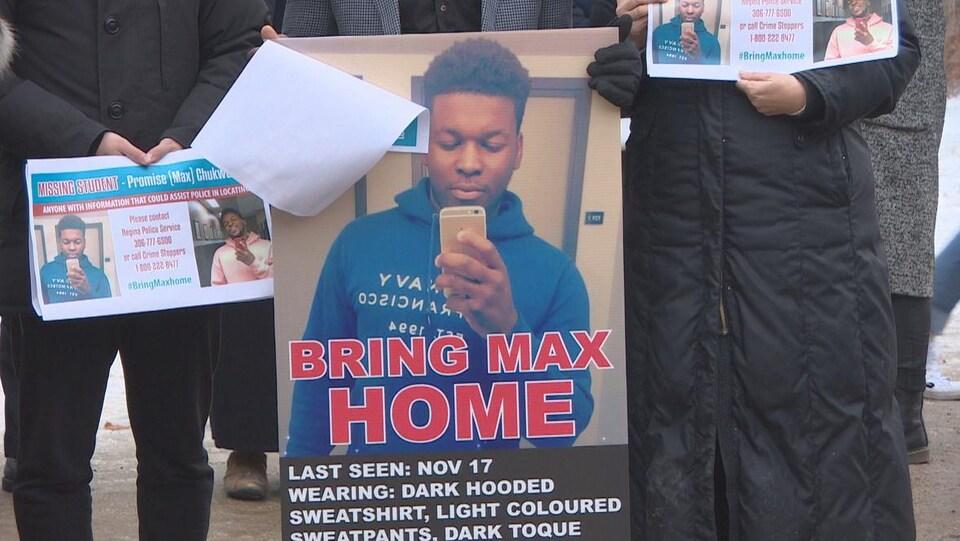Des personnes tiennent des affichent de Promise « Max » Chuckwudum qui est porté disparu depuis le 17 novembre à Regina