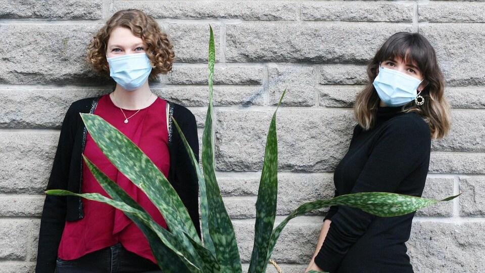 Deux femmes tiennent une plante à deux dans les mains. Elles portent un masque.