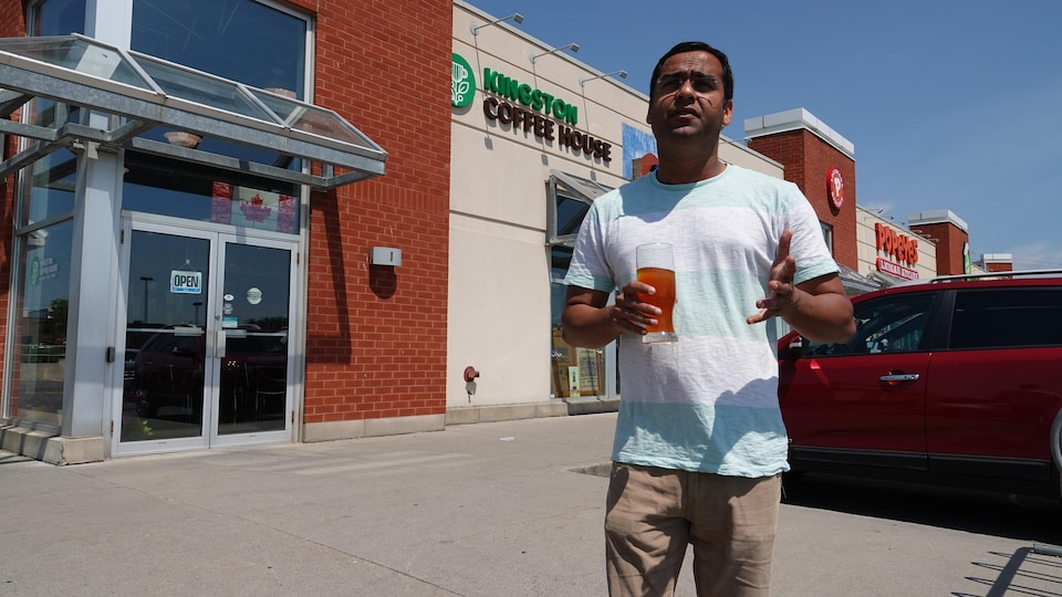 Il se tient devant l'édifice où se trouve son café, un thé glacé à la main.