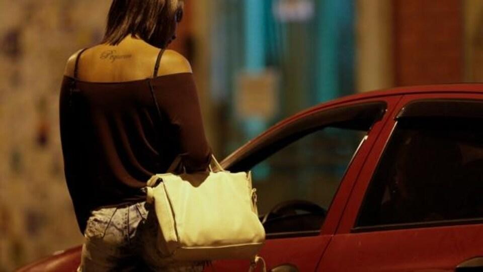Une femme dans la rue s'adresse au conducteur d'une voiture.