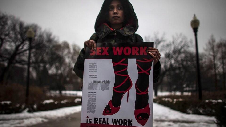 Une femme tient une affiche sur laquelle il est écrit, en anglais, que le travail sexuel est un vrai emploi, lors d'une manifestation devant la Cour suprême du Canada en 2013.