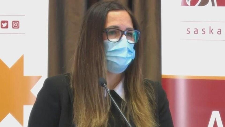 Une femme aux cheveux, une paire de lunettes sur le nez et portant un masque s'exprime face à des micros posés devant elle. Il s'agit de Lisa Broda.