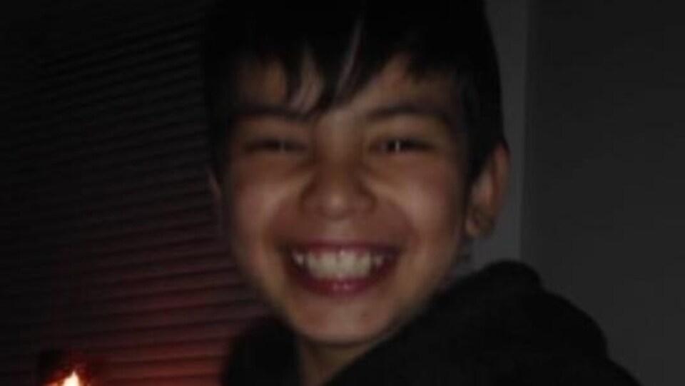 Visage d'un adolescent souriant à pleines dents.