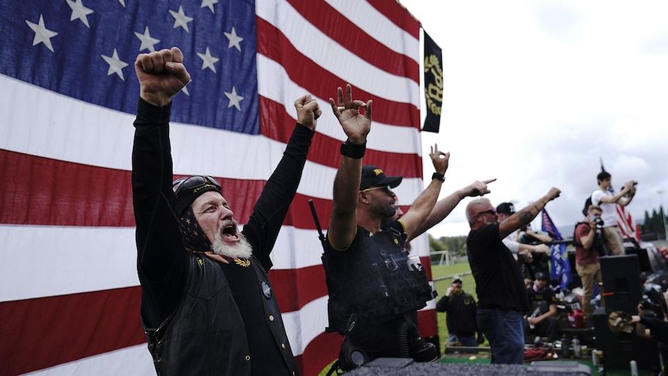 Des hommes armés lèvent les bras au ciel.
