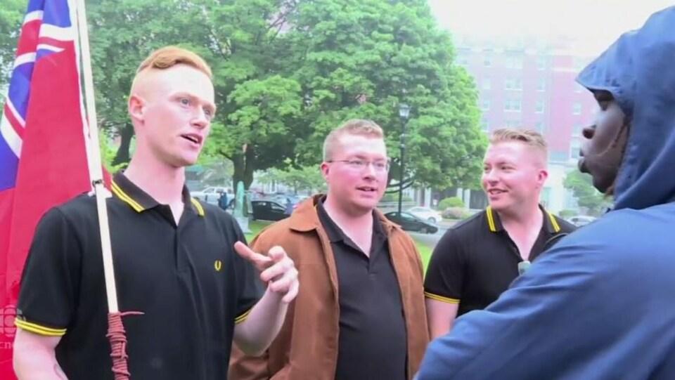 Trois membres canadiens des Proud Boys, vêtus de polo noir et jaune, discutent en tenant le Red Insign canadien, ancêtre du drapeau officiel.